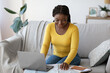 Leinwandbild Motiv Positive Black Lady Planning Vacation With Laptop And Map At Home