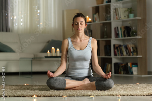 Obraz Woman doing yoga exercise in the night at home with candles - fototapety do salonu