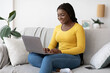 Smiling African American Lady Using Laptop Computer On Couch At Home