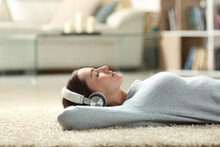 Relaxed Woman Listening To Music With Headphones At Home