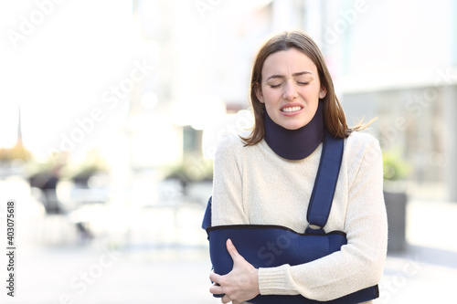 Woman suffering with broken arm on a sling in the street Poster Mural XXL