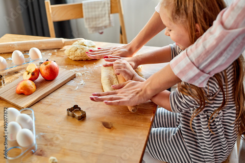 Tela cropped mother teaches daughter prepare dough in the kitchen with fun, close-up