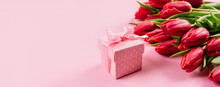 Gift Box With A Pink Ribbon In White Polka Dots On A Background Of A Bouquet Of Red Tulips With Copy Space For Text. Wallpaper Or Banner For Gift Shop, Flower Shop Or Jewelry Store. Valentine Day