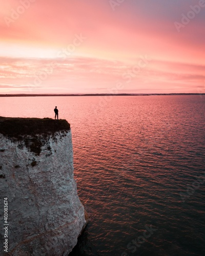 Fototapeta a traveler standing on a remote rock in front of the sea in a dreamy scenery whi