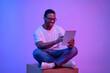 Leinwandbild Motiv Young black freelancer guy sitting with digital tablet under luminous neon light