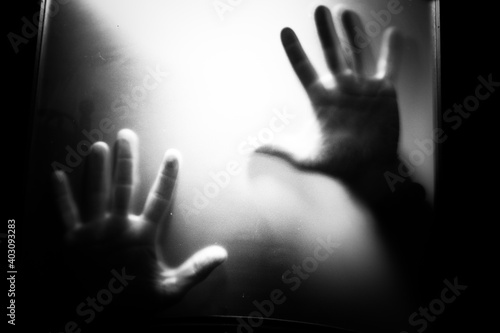 Fototapeta premium scary picture of hands behind glass