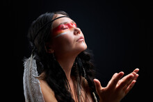 Model Wearing Native American Feathers Is Shamaning Or Praying Isolated Over Black Background. Ethnic Woman With Feathers On Head Stand With Closed Eyes