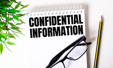 CONFIDENTIAL INFORMATION Is Written In A White Notebook Next To A Pencil, Black-framed Glasses And A Green Plant.