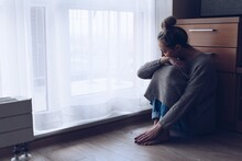 A Devastated Sad Woman Is Sitting On The Floor In Her Living Room Looking At The Window. She Is Depressed.
