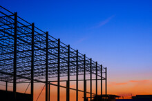 Silhouette Low Angle View Of Large Industrial Building Structure In Construction Site Area Against Colorful Twilight Sky Background