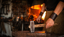 Blacksmith Performs The Forging Of Hot Glowing Metal On The Anvil