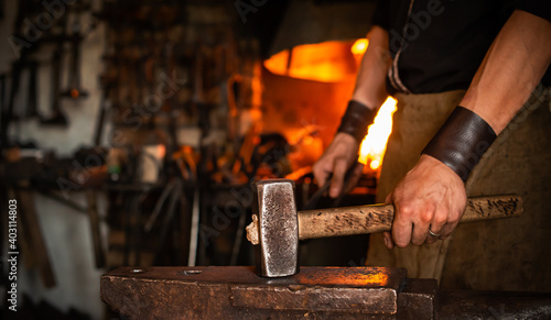 Fotografie, Tablou blacksmith performs the forging of hot glowing metal on the anvil