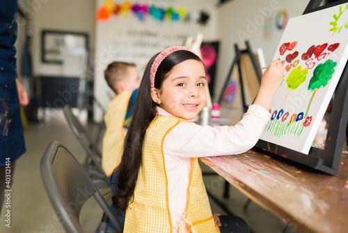 Slika na platnu Beautiful latin kid is smiling during her painting class