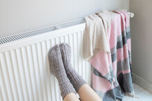 Woman Is Warm Knitted Woolen Socks Near A Home Heater In Cold Winter Time. Using Heater At Home In Winter.
