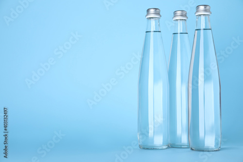 Obraz Glass bottles with water on light blue background, space for text - fototapety do salonu