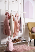 Rack With Stylish Warm Clothes, Shoes And Accessories In Modern Dressing Room