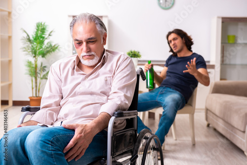 Obraz Old man in wheel-chair and young bad caregiver indoors - fototapety do salonu
