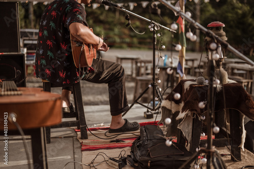 A musician wearing a Hawaiian shirt plays the guitar on stage at a music festival..Concert,mini concert and music festivals.