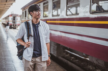 Portrait Asian Man Walking Onto A Train At A Train Station For A Vacation.Travel Concept. Man Traveler Tourist Walking At Train Station.