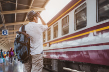Asian Man Traveler With Backpack Waiting For Train, Asian Backpacker With Hat Standing On Railway Platform At Bangkok Train Station. Holiday, Journey, Trip And Summer Travel Concept.