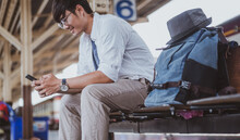 Asian Man Returning From A Vacation On A Train Journey, And He Is Using A Smartphone To Pick Up His Relatives At The Station.Holiday, Journey, Trip And Summer Travel Concept.