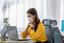 New Normal Of Asian Woman In Yellow Shirt Wearing Surgical Face Mask Working With Computer Laptop Thinking To Get Ideas And Requirement In Business Startup At Modern Office Or Co-working Space