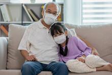 Asian Elderly Grandfather Hug Grandchild And Wearing Face Mask On Sofa At Home Protect Virus Infection