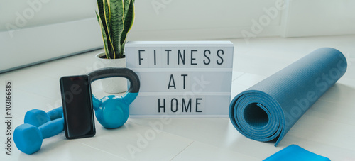 Fototapeta Fitness at home lightbox sign in living room for online workout on phone app training indoors with dumbbell weights and resistance bands on yoga mat banner background. obraz