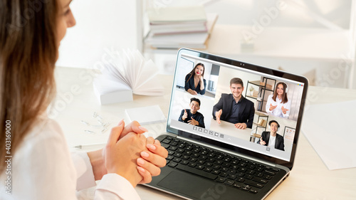 Obraz Video call. Virtual meeting. Online teamwork. Pandemic WFH. Ambitious diverse multiracial team greeting new employee on laptop screen at light modern home office. - fototapety do salonu
