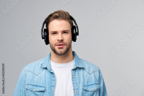 Obraz Close up portrait of cheerful young man enjoying listening to music wearing casual jeans outfit - fototapety do salonu