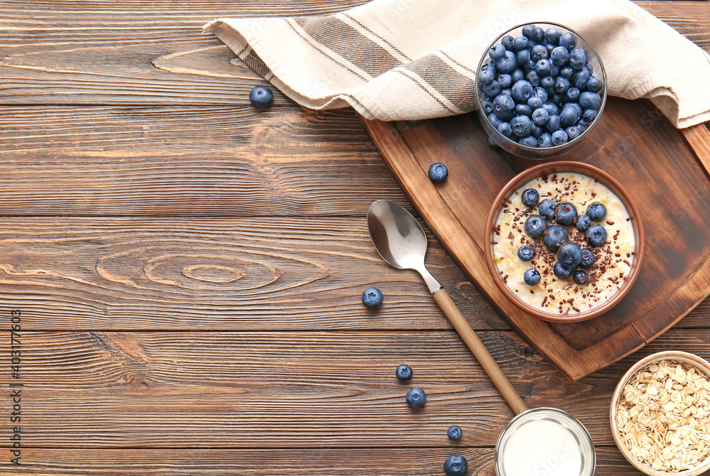 Fototapeta Bowl with tasty oatmeal and blueberry on wooden table