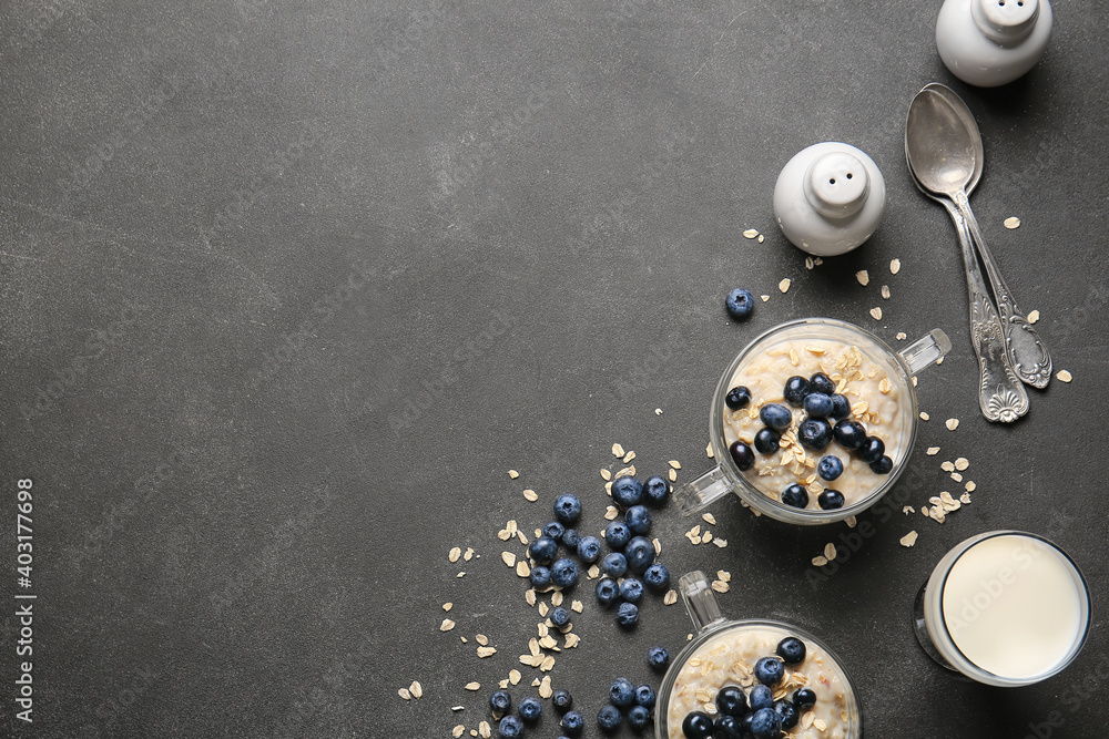 Fototapeta Bowls with tasty oatmeal and blueberry on dark table