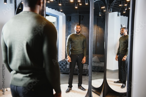 Stylish casual african american man at fitting room clothes store, looking on mirror Fotobehang