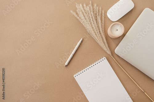 Flatlay of spiral flip notebook with blank paper sheet. Laptop, pampas grass, stationery on beige peachy pastel background table. Minimalist home office desk workspace. Top view mockup copy space.