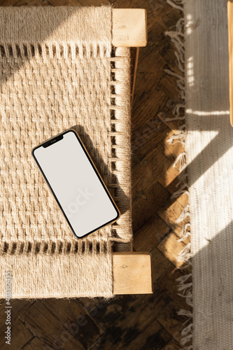 Obraz Blank screen smart phone on rattan chair. Flat lay, top view. Copy space mockup template. Warm sunlight shadows. - fototapety do salonu