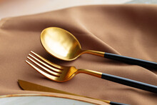 Set Of Golden Cutlery On Napkin Close Up