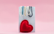 Red Heart And Pearl Beads On White Package On Pink Background. Copy Space.