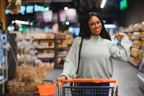 Tela African american woman with shopping cart trolley in the supermarket store