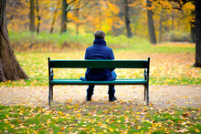 Lonely Man Sitting On A Wooden Bench Outdoors In A Park In Autumn Day