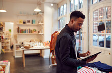 Male Small Business Owner Checks Stock In Shop Using Digital Tablet