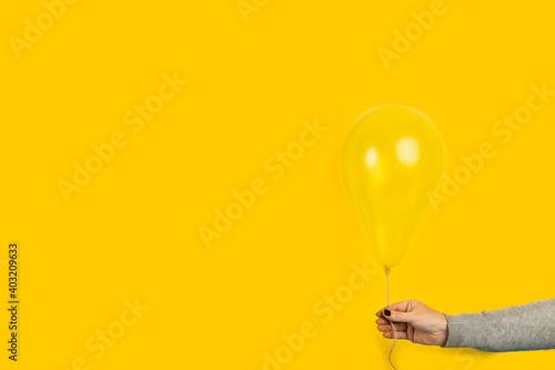 Photo Mano de mujer sosteniendo un globo amarillo sobre un fondo amarillo liso y aislado