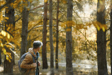 Traveler Man With Backpack Walking In Forest, Enjoying Beautiful Nature In Woods And Sun Lights. Concept Adventure Active Vacations Outdoo