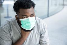 Symptometic Black African Man Wearing Hygienic Face Mask And Having Sore Throat Due To Covid-19 Flu Symptom