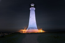 Fire And Sparks Surround The Base Of A Lighthouse Perched On Top Of A Hill