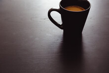 Black Cup Of Hot Coffee On Dark Wooden Background, Back Lit