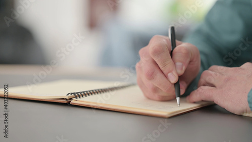 Fototapety, obrazy: Close up of Hands of Man Writing in Notebook