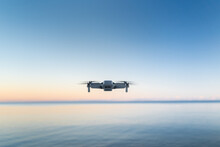 A Micro Drone Hovers In The Air Above A Water Horizon
