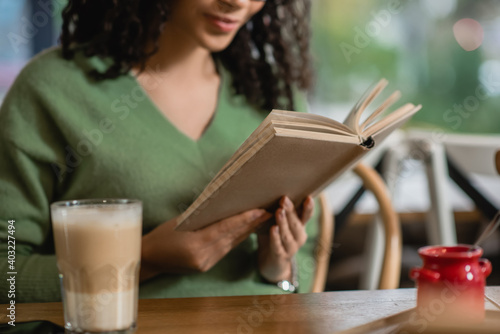 Obraz partial view of african american woman reading book near glass with latte on blurred foreground - fototapety do salonu