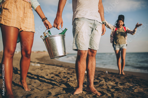 Obraz Young friends enjoying a walk on the beach party on a sunny day holding beer. - fototapety do salonu