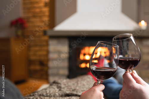Obraz Couple in love sitting in a cozy room with fire place on a sofa with glass of wine. Family and love concept. - fototapety do salonu